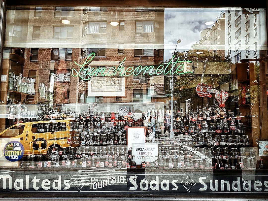 Looking in the window at all the Coca-Cola bottles in the Lexington Candy Shop.